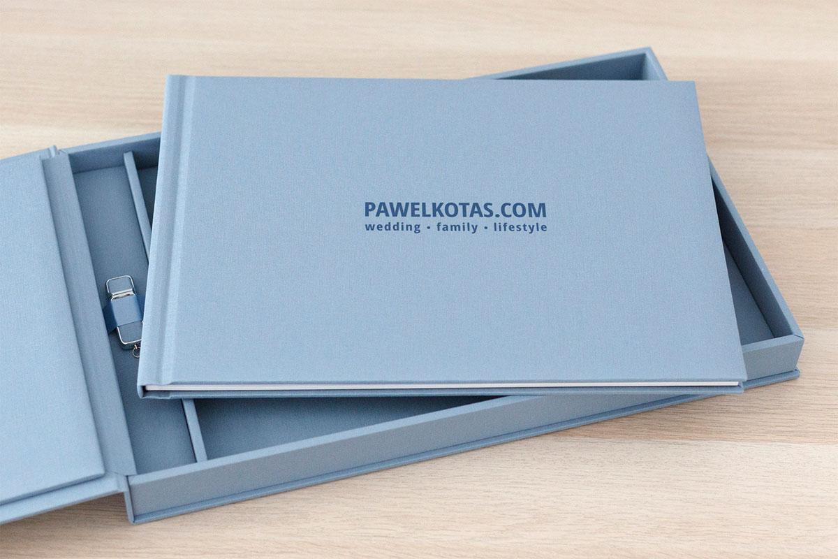 Elegancka błękitna książka ślubna w pudełku z dołączonym pendrive, na którym znajdują się zdjęcia ślubne w wersji cyfrowej