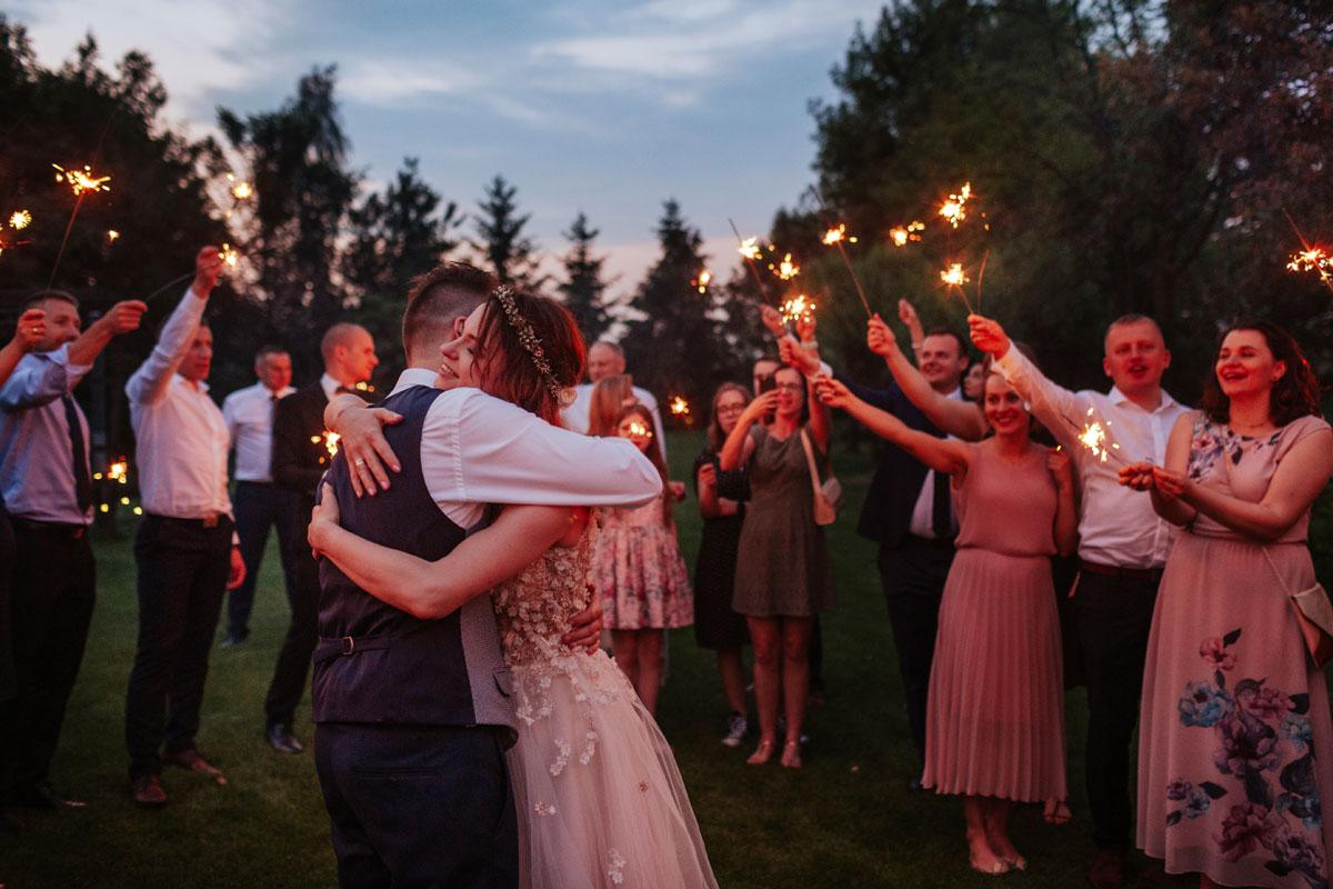 Para Młoda pośród zimnych ogni w towarzystwie gości weselnych