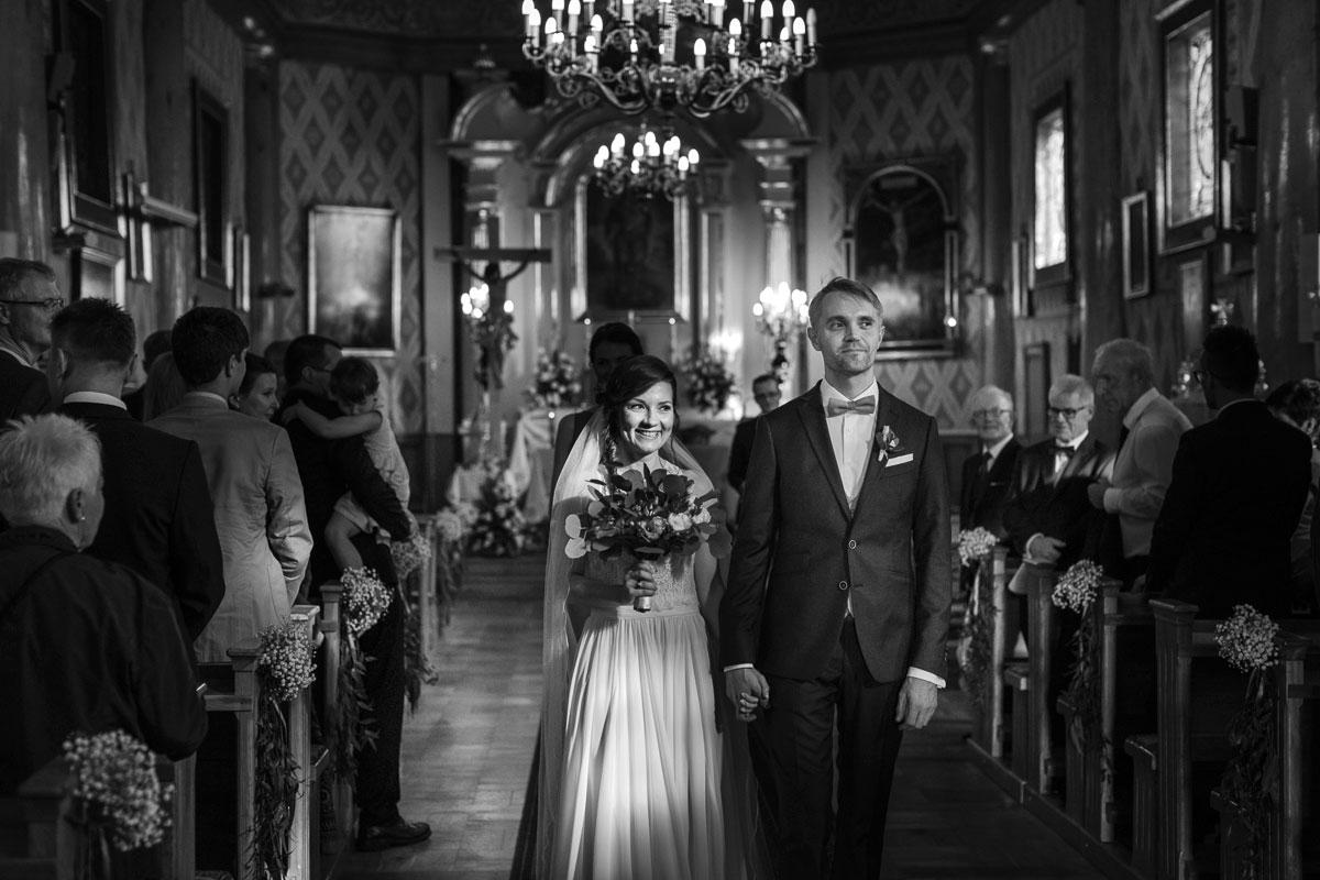Para Młoda wychodząca z kościoła po ceremonii ślubnej
